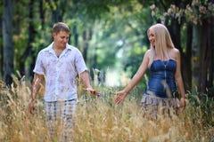 El hombre joven y la muchacha enamorados caminan en alta hierba Foto de archivo libre de regalías