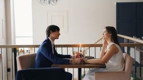 El hombre joven y la mujer de los pares felices están hablando llevando a cabo las manos que se sientan en restaurante el fecha j almacen de metraje de vídeo