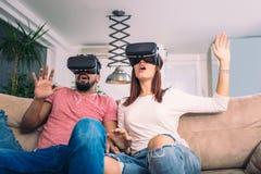 El hombre joven y la mujer en ropa casual llevan los vidrios de la realidad virtual Imagenes de archivo
