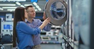 El hombre joven y la mujer en tienda de dispositivos eligen comprar la lavadora para el hogar Abra la puerta que mira en el tambo metrajes
