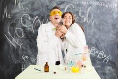 El hombre joven y la mujer en un laboratorio de química crearon un elixir imagenes de archivo