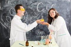 El hombre joven y la mujer en un laboratorio de química crearon un elixir imagen de archivo