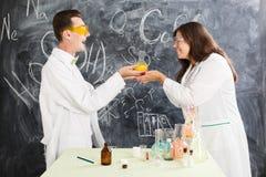 El hombre joven y la mujer en un laboratorio de química crearon un elixir fotos de archivo
