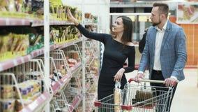 El hombre joven y la mujer felices eligen productos en supermercado almacen de metraje de vídeo