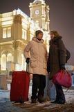 El hombre joven y la mujer joven se colocan con el bolso rojo grande de la carga rodada Imágenes de archivo libres de regalías