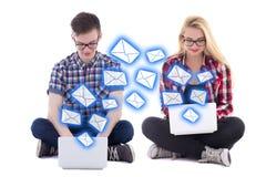 El hombre joven y la mujer que se sientan con los ordenadores portátiles y que envían mensajes es Fotos de archivo