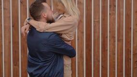 El hombre joven y la mujer se están encontrando en la calle, hombre está levantando a la muchacha en las manos almacen de video