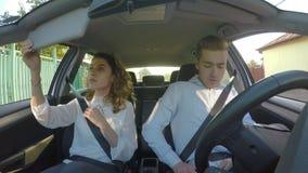 El hombre joven y la novia consiguen en el coche y se preparan para dejar y para poner sus cinturones de seguridad almacen de video