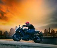 El hombre joven y la seguridad se adaptan a la motocicleta grande que monta contra beautifu Imagenes de archivo