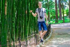 El hombre joven y sonriente con una cámara se coloca cerca de un alto bambú imagen de archivo libre de regalías