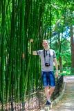 El hombre joven y sonriente con una cámara se coloca cerca de un alto bambú Imágenes de archivo libres de regalías