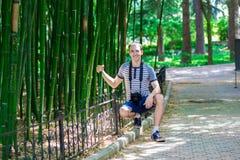 El hombre joven y sonriente con una cámara se coloca cerca de un alto bambú foto de archivo