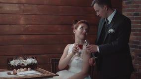 El hombre joven y su muchacha hermosa golpean los vidrios, despu?s beben el vino, durante cena en un restaurante, c?mara lenta almacen de video