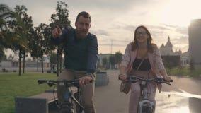 El hombre joven y su novia están montando las bicis en una ciudad por la tarde del verano almacen de metraje de vídeo