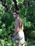 El hombre joven y una madera verde Imagen de archivo libre de regalías