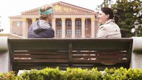 El hombre joven y una mujer se sientan en el banco y hablan alegre metrajes