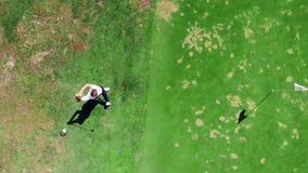 El hombre juega a golf en un curso verde almacen de metraje de vídeo