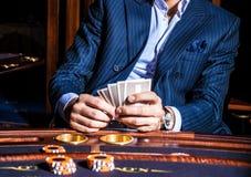 El hombre juega a tarjetas en casino Foto de archivo libre de regalías
