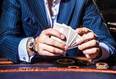 El hombre juega a tarjetas en casino foto de archivo