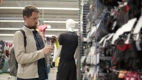 El hombre juguetón está mirando una botella plástica para el agua en una tienda del deporte metrajes
