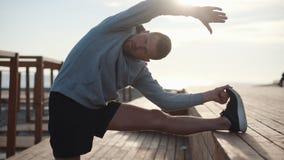El hombre juguetón hermoso está estirando sus piernas en el entrenamiento de la mañana al aire libre almacen de metraje de vídeo