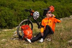 El hombre juguetón para el completar un ciclo y tiene un resto en el valle Foto de archivo