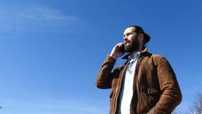 El hombre jura activamente con el interlocutor en el teléfono almacen de video