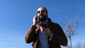 El hombre jura activamente con el interlocutor en el tel?fono metrajes