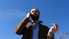 El hombre jura activamente con el interlocutor en el tel?fono almacen de video