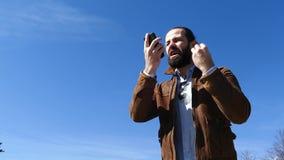 El hombre jura activamente con el interlocutor en el tel?fono almacen de metraje de vídeo