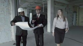 El hombre, la mujer, el afroamericano en traje y el casco consideran el modelo dentro del emplazamiento de la obra almacen de metraje de vídeo