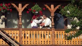 El hombre, la mujer y el bebé con ropa tradicional en el balcón de madera de la casa, parents besar al niño, retrato de la famili metrajes