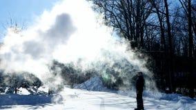 El hombre lanza el agua hirvienda en menos aire escarchado del invierno de 20 grados el día soleado en Minnesota almacen de video