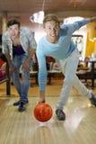 El hombre lanza la bola en el bowling; el amigo mira puntería fotos de archivo
