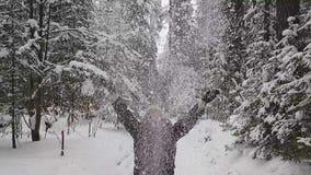 El hombre lanza para arriba nieve en la madera Cámara lenta metrajes