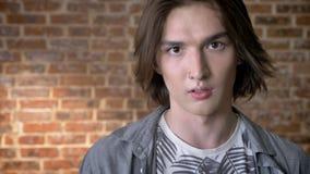 El hombre largo joven del pelo con el anillo de nariz está mirando en la cámara, estando enojado, fondo metrajes