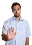 El hombre latino en una camisa azul dice la parada Fotografía de archivo