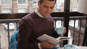 El hombre lee el libro en el café almacen de video