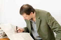 El hombre lee el periódico en una tabla Fotos de archivo libres de regalías