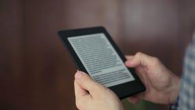 El hombre lee un Ebook en su tableta interior metrajes