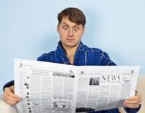 El hombre lee un periódico con una admiración Foto de archivo libre de regalías