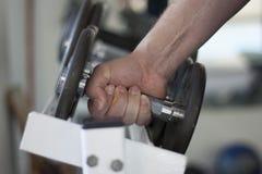 El hombre levanta el peso de la pesa de gimnasia del estante en gimnasio Fotografía de archivo