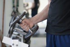 El hombre levanta el peso de la pesa de gimnasia del estante en gimnasio Fotos de archivo