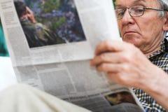 El hombre leyó los periódicos foto de archivo