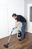 El hombre limpia el plano con la aspiradora foto de archivo