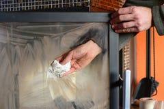 El hombre limpia el vidrio sucio de la chimenea por la toalla de papel Fotografía de archivo