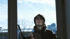 El hombre limpia el limpiador con una ventana sucia del exterior, cámara lenta almacen de metraje de vídeo