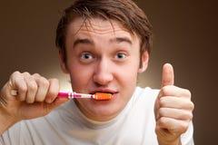 El hombre limpia los dientes Imagen de archivo libre de regalías