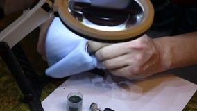 El hombre limpia un anillo de oro del joyero después de pulir almacen de video