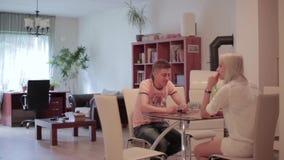 El hombre lindo y la mujer rubia se sientan en la tabla, hablan y notan el helicóptero nano que vuela metrajes